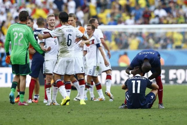 7月4日、サッカーのW杯ブラジル大会準々決勝フランス対ドイツ。試合後、喜ぶドイツ選手たちの横でピッチに座り込むフランスのアントワーヌ・グリエスマンと声をかけるエリアカン・マンガラ(2014年 ロイター/Darren Staples)