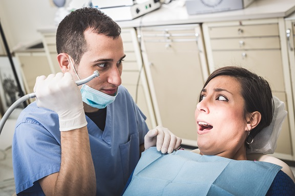 Dentist Scaring Patient with the Drill. Dentist is a Man, Patient is a Woman. Dentist is Holding Drill like a Knife and Patient looks Scared. Funny Representation of Dental Fear.